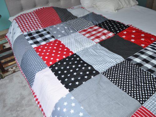 sprei, quilt, deken, zelfgemaakt van katoen in blokken rood, zwart, grijs, wit.