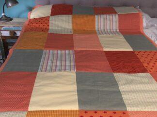 zelfgemaakt sprei of quilt van katoenen stof blokken oranje, geel, rood