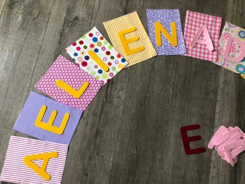 Handgemaakte slingers, vlaggenlijn met naam, unieke naamvlag, naamslinger, katoenen vlaggetjes, stoffen slinger met naam, geboorteslinger, zelf samenstellen, vrolijk, roze, wit, paars, bloemen, geel
