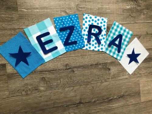 Handgemaakte slingers, unieke naamvlag, vlaggenlijn met naam, naamslinger, katoenen vlaggetjes, stoffen slinger met naam, lichtblauw, donkerblauw, ster, ruit, stip, vilten letters